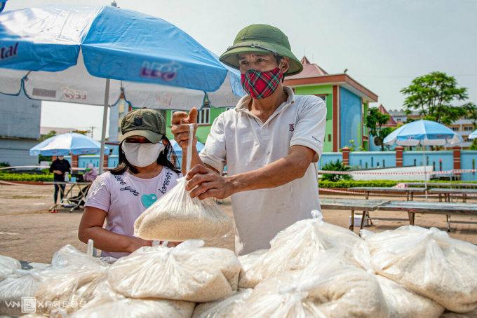 Anh Cường và con gái đầu lòng nhận gạo hỗ trợ cho công nhân có hoàn cảnh khó khăn. Ảnh: Thanh Huế.