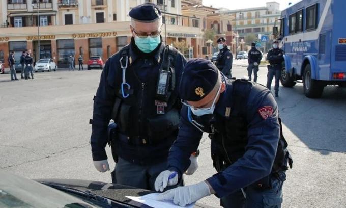 Cảnh sát kiểm tra một tài xế ởOstia, Italy ngày 13/4. Ảnh: Reuters.