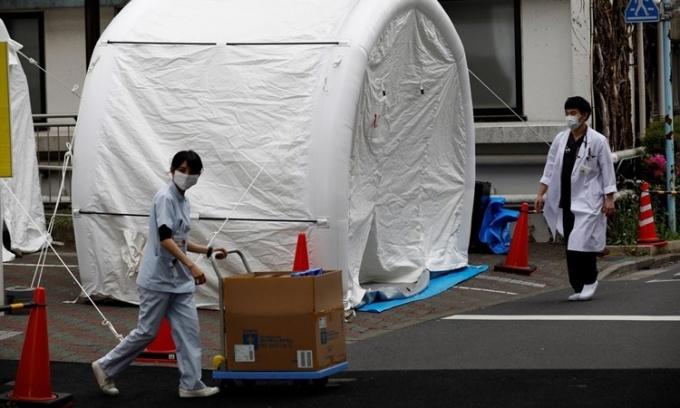 Nhân viên y tế bước qua một chiếc lều dùng để xét nghiệm nCoV tại bệnh viện đa khoa Kawakita ở Tokyo, Nhật Bản, ngày 17/4. Ảnh: Reuters.
