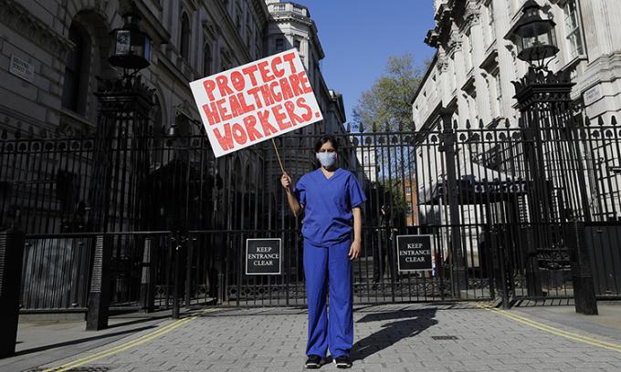 Nữ bác sĩMeenal Viz cầm bảng biểu tình bên ngoài số 10 phố Downing, London, ngày 19/4. Ảnh: AP.