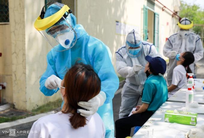 Nhân viên Trung tâm Kiểm soát bệnh tật thành phố lấy mẫu xét nghiệm các công nhân tại Thủ Đức chiều 20/4. Ảnh: Quỳnh Trần