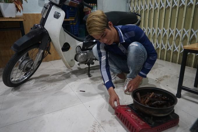 Anh Lò Việt Hoàng đun nồi quế để xông cửa hàng trên phố Nghĩa Tân. Ảnh: Gia Chính