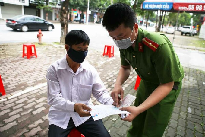 Ông Nguyễn Văn Chuyên (áo trắng) được cán bộ phát phiếu số thứ tự chuẩn bị vào giải quyết thủ tục sáng 23/4. Ảnh: Nguyễn Hải.
