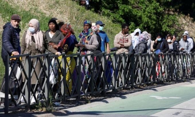 Người dân xếp hàng chờ nhận thực phẩm ở xãClichy-sous-Bois, ngoại ô thủ đô Paris của Pháp hôm 22/4. Ảnh: Reuters.