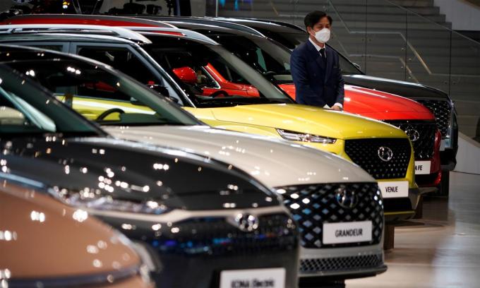 Một nhân viên đeo khẩu trang đứng đợi khách hàng tại một đại lý Hyundai ở Goyang, Hàn Quốc, hôm 21/4. Ảnh: Reuters