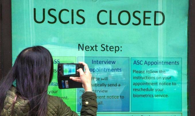 Một phụ nữ đứng trước bảng thông báo đóng cửa do Covid-19 của văn phòng Cơ quan Di trú và Nhập trịch Mỹ (USCIS) ở Tukwila, Washingon, hôm 3/3. Ảnh: AP