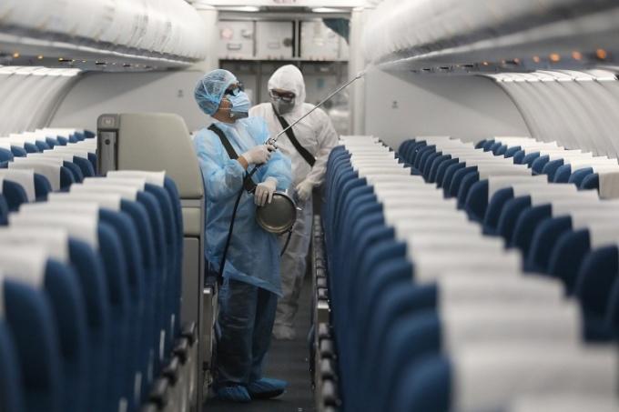 Nhân viên y tế phun thuốc khử trùng trên một chuyến bay của Việt Nam ngày 13/3. Ảnh: Ngọc Thành.
