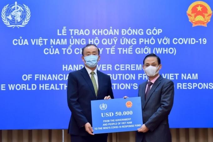 Thứ trưởng Ngoại giao Việt Nam Lê Hoài Trung, phải, và ông Kidong Park, Đại diện WHO, trong lễ trao tượng trưng ngày 24/4 tại Hà Nội. Ảnh: BNGVN.