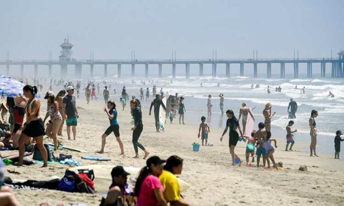 Người dân tràn ngập bãi biển tại thành phốHuntington Beach, bang California, Mỹ hôm 25/4. Ảnh: Reuters.