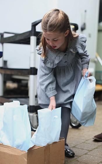 Công chúa Charlotte xách túi đựng thực phẩm để đi tặng cho những người dân quanh khu vực Sandringham. Ảnh: Cung điện Kensington.
