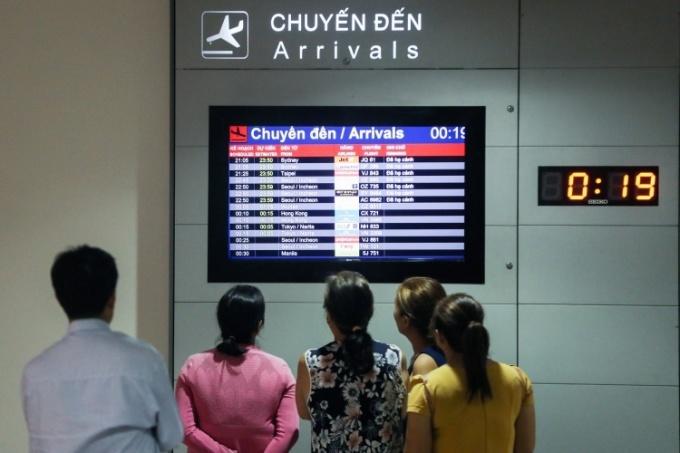 Người Việt theo dõi chuyến bay đến tại sân bay Tân Sơn Nhất, TP HCM ngày 18/1. Ảnh: Quỳnh Trần.