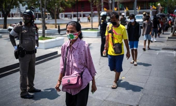 Người dân đeo khẩu trang xếp hàng nhận bữa ăn miễn phí tại một trường học ở thủ đô Bangkok, Thái Lan, ngày 2/5. Ảnh: Reuters.