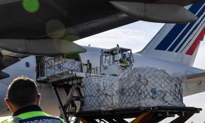 Công nhân dỡ hàng khỏi máy bay chở khẩu trang từ Trung Quốc trên đường băng sân bayParis Charles de Gaulle ở Roissy, Pháp hôm 30/4. Ảnh: AFP.