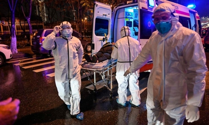 Nhân viên y tế di chuyển bệnh nhân tại Vũ Hán ngày 25/1. Ảnh: AFP.