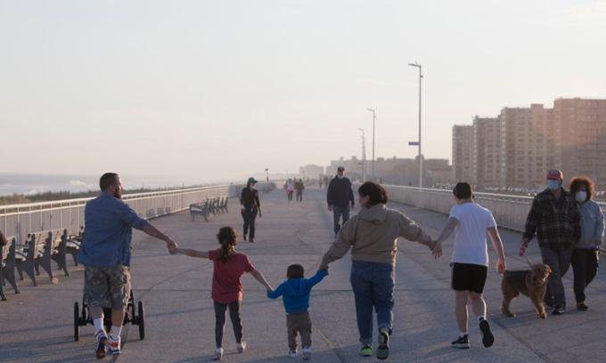 Một gia đình Mỹ đi dạo trên con đường gần bãi biểnRockaway ởQueens, New York, chiều 2/5. Ảnh: NYTimes.