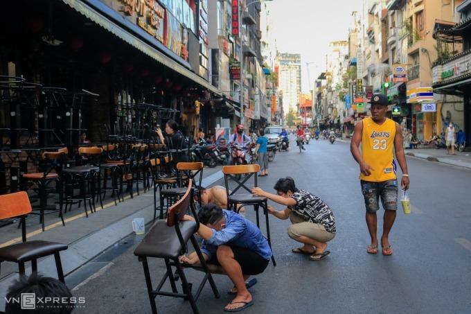 Nhân viên một quán bar ở phố Tây Bùi Viện, quận 1 sơn sửa lại bàn ghế để chuẩn bị mở cửa trở lại từ hôm 23/4, ngay sau khi hết lệnh cách ly theo Chỉ thị 16 của Thủ tướng. Ảnh: Quỳnh Trần