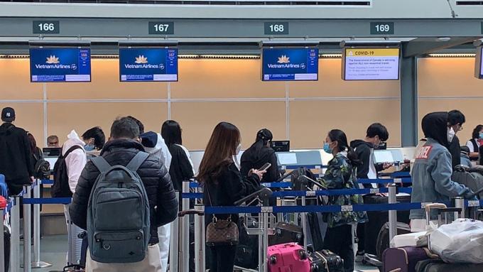 Các công dân Việt Nam làm thủ tục lên chuyến bay về nước từ Vancouver, Canada. Ảnh: Bộ Ngoại giao