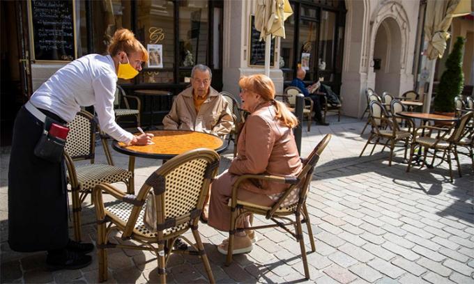Nữ bồi bàn phục vụ hai khách hàng ở quán cà phê Prag tại Schwerin, Đức ngày 9/5. Ảnh: AFP.