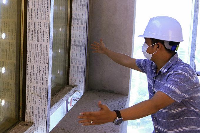 Chủ đầu tư toà nhà 30 tầng đang tính toán việc dán phủ film để che bớt diện tích kính vàng gây loá mắt người đi đường. Ảnh: Ngọc Trường.