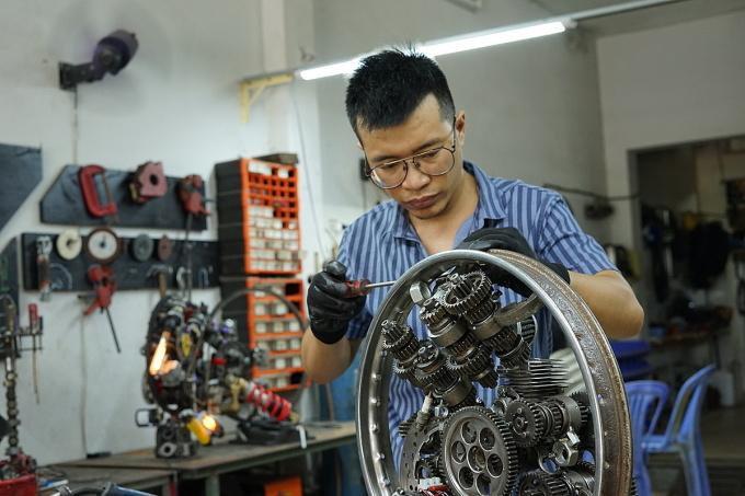Tuấn Anh lắp đặt một chiếc đồng hồ cơ khí tại xưởng của mình. Ảnh: Thành Nhạn