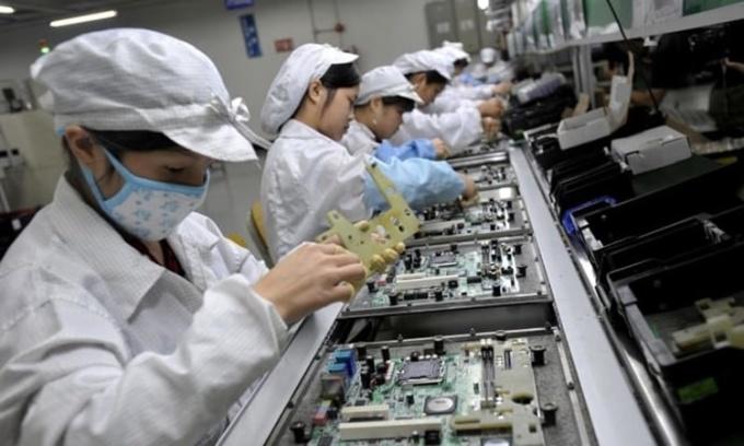 Công nhân lắp ráp linh kiện điện tử tại một nhà máy của Foxconn ở Thâm Quyến, Trung Quốc. Ảnh: AFP.