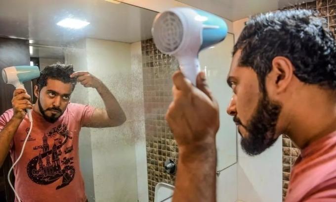 Suraj Balakrishnan, giám đốc một công ty truyền thông, 30 tuổi, sấy tóc sau khi tắm tại nhà riêng ở Mumbai hôm 6/2. Ảnh: AFP.