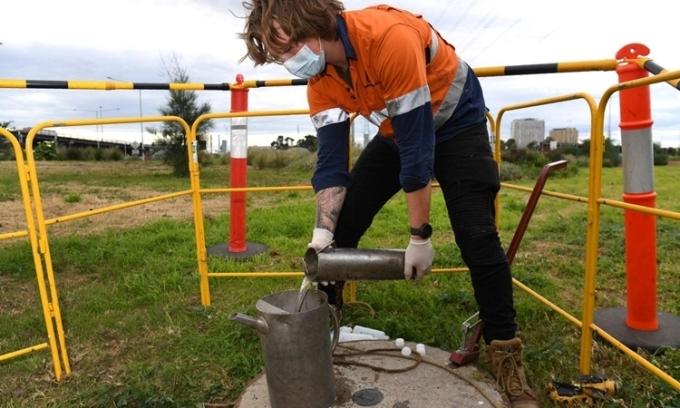 Nhân viên lấy mẫu chất thải từ một cống thoát nước ởMelbourne. Australia, hôm 19/5. Ảnh: AFP.