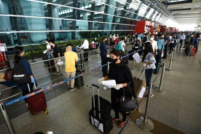 Hành khách xếp hàng vào sân bay New Delhi sáng sớm nay. Ảnh: AFP