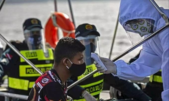 Nhân viên y tế chính phủ Brazil phối hợp cùng cảnh sát kiểm tra thân nhiệt cho một khách đi tàu ở bang Para hôm 27/5. Ảnh: AFP.