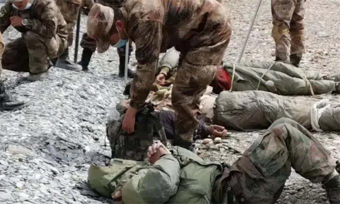 Binh sĩ Trung Quốc đứng cạnh nhóm lính Ấn Độ nằm dưới đất sau vụ ẩu đả gần hồ Pangong Tso. Ảnh: SCMP.