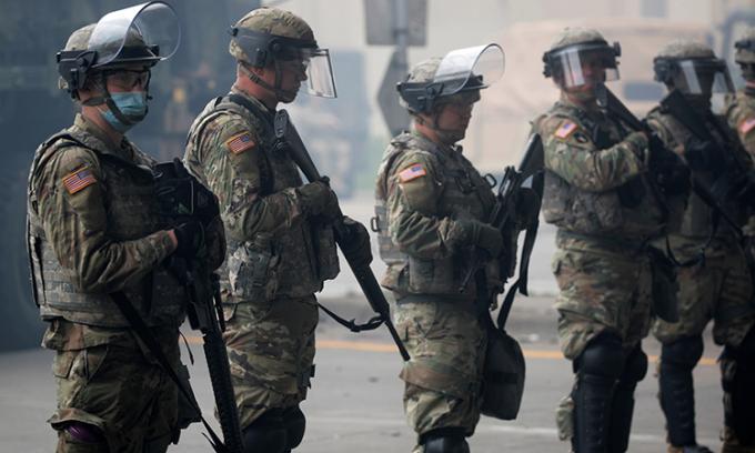 Vệ binh Quốc gia bang Minnesota được triển khai tại thành phố Minneapolis, trên tay áo họ có dán quốc kỳ Mỹ, ngày 29/5. Ảnh: Reuters.