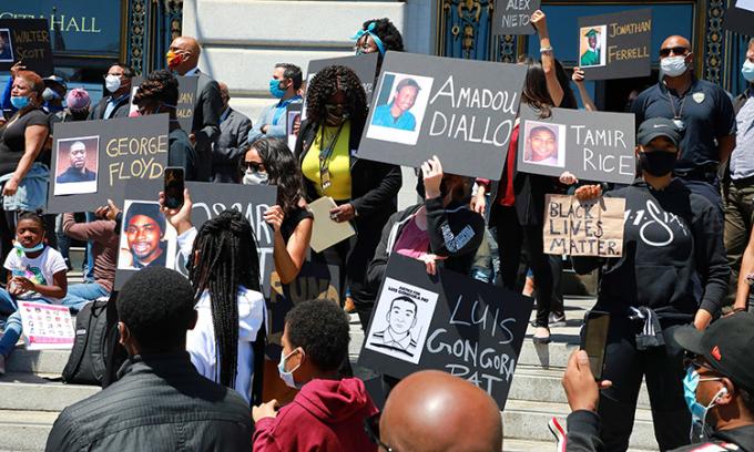 Người biểu tình giơ bảng tên và ảnh người da màu từng chết vì cảnh sát trước tòa thị chính ởSan Francisco, hôm 1/6. Ảnh: NYTimes.