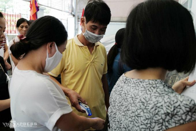 Mỗi buổi sáng, anh Ứng Doãn Hùng, nhân viên CDC Cầu Giấy đo thân nhiệt cho khoảng 700 - 800 người đến giao dịch. Ảnh: Ngọc Thành.
