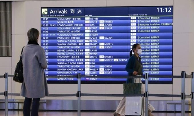 Hành khách theo dõi lịch trình bay tại một sân bay ở Tokyo, Nhật Bản hồi tháng 1. Ảnh: Kyodo News.