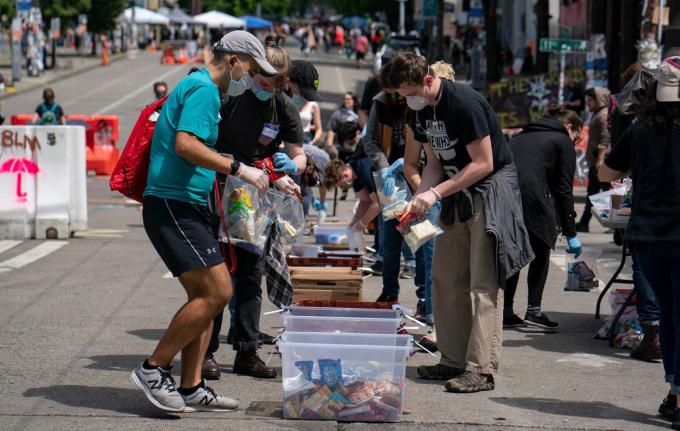 Các tình nguyện viên đóng gói đồ cung cấp cho người vô gia cư trong khu phố. Ảnh: NY Times.