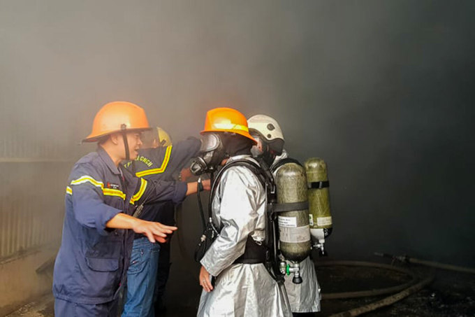 Lính cứu hoả thảo luận nhanh phương án dập lửa. Ảnh: Hồ Nam.