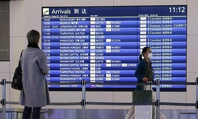 Hành khách theo dõi lịch trình bay tại một sân bay ở Tokyo, Nhật Bản, hồi tháng 1. Ảnh:Kyodo News.