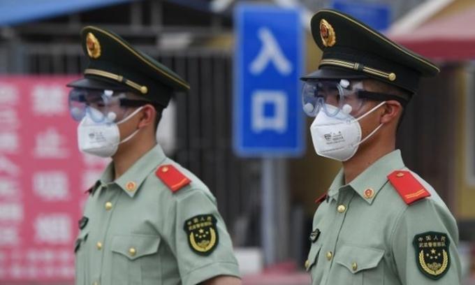 Cảnh sát đeo khẩu trang đứng gác bên ngoài chợ Tân Phát Địa ở Bắc Kinh hôm 13/6. Ảnh: AFP.