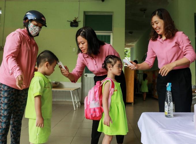 Giáo viên tại trường Mầm non Thị trấn Củ Chi 2 (TP HCM) đo nhiệt độ và hướng dẫn học sinh rửa tay bằng dung dịch sát khuẩn trước khi vào lớp. Ảnh: Quỳnh Trần.