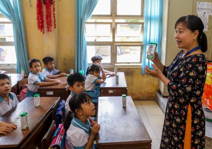 Giáo viên trường Tiểu học Thị trấn Củ Chi (TP HCM) hướng dẫn cho các em uống sữa đúng cách. Ảnh: Quỳnh Trần.