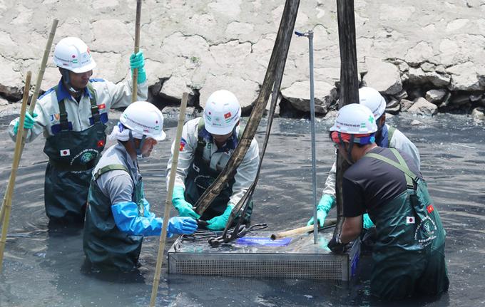 Đơn vị thí điểm làm sạch sông Tô Lịch bằng công nghệ nano hạ thiết bị xuống sông hồi tháng 5/2019. Ảnh: Võ Hải.
