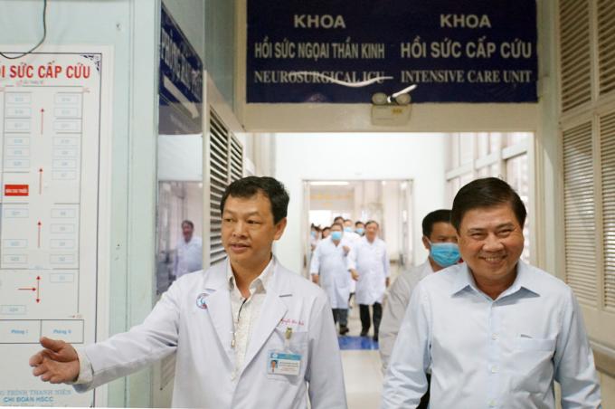 Chủ tịch UBND TP HCM Nguyễn Thành Phong (phải) cùng Bác sĩ Nguyễn Tri Thức, Giám đốc Bệnh viện Chợ Rẫy sau khi bước ra phòng điều trị bệnh nhân 91 tại khoa Hồi sức cấp cứu. Ảnh: Mạnh Tùng.