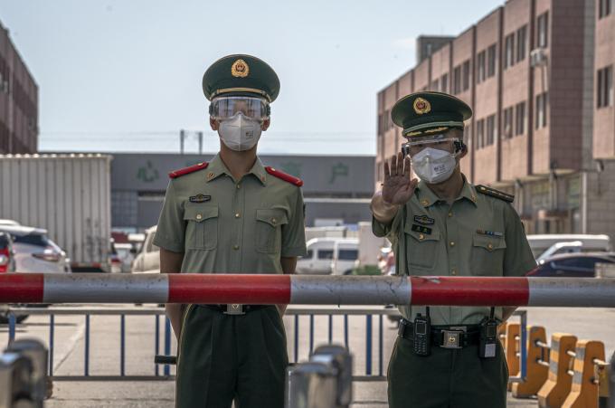 Vũ cảnh Trung Quốc canh gác trước chợ Tân Phát Địa ở Bắc Kinh. Ảnh: Reuters.