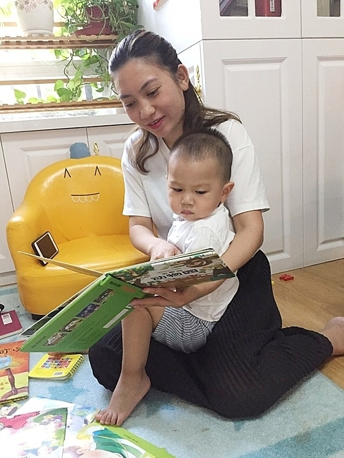 Chị Quỳnh đọc truyện cùng bé Tôm, 2 tuổi, tại nhà riêng hôm 19/6. Ảnh: NVCC