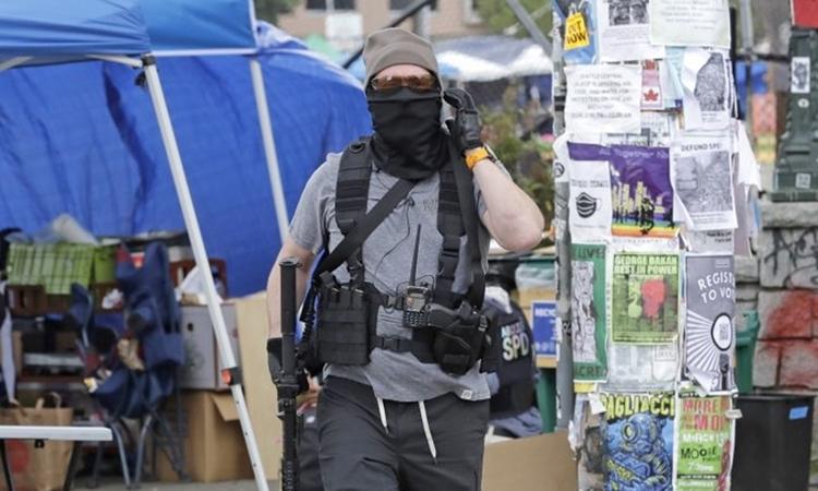 Một tình nguyện viên cầm súng tại CHOP ở Seattle ngày 20/6. Ảnh: AP.