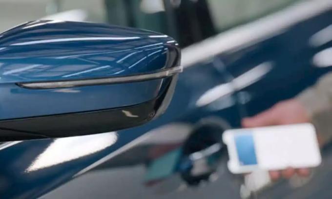 Đưa điện thoại thông minh lại gần tay nắm cửa, tài xế có thể mở khóa xe thông qua thiết bị di động. Ảnh: Apple