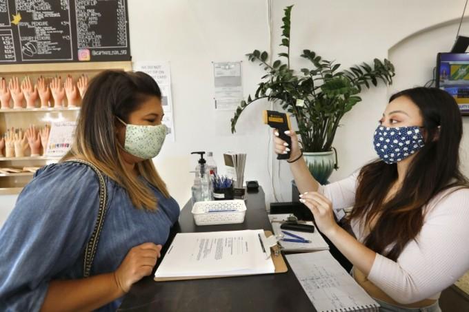 Christina Dinh đo thân nhiệt cho khách tạitiệmCaptivate Nail & Spa. Ảnh: LA Times