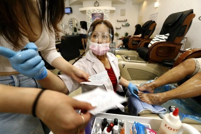 Bà chủCrystal Trang Luong làm móng chân cho khách tại tiệmCaptivate Nail & Spa ở thành phố Fullerton, bang California hôm 19/6. Ảnh: LA Times