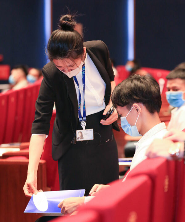 Một giám thị kiểm tra tài liệu của ứng viên trước giờ làm bài.