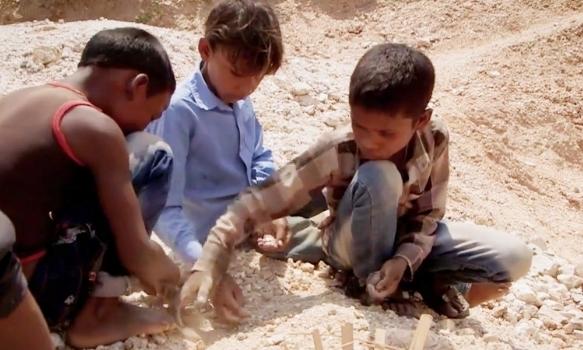 Một nhóm trẻ em Ấn Độ tuổi từ 6-9 nhặt mica trên phần lộ thiên của khu khai thác mỏ dưới ánh nắng thiêu đốt của tháng 6. Ảnh: Aljazeera.
